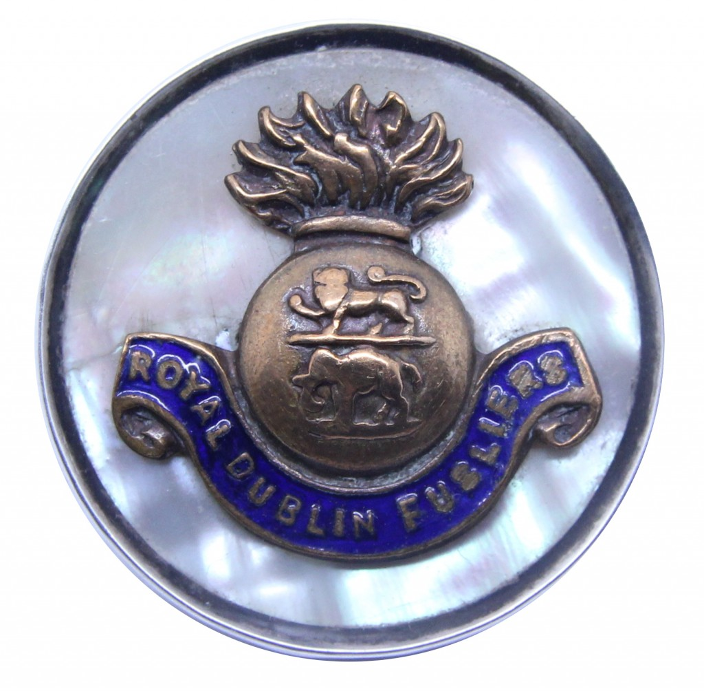Mother of pearl backed badge with a white metal rim